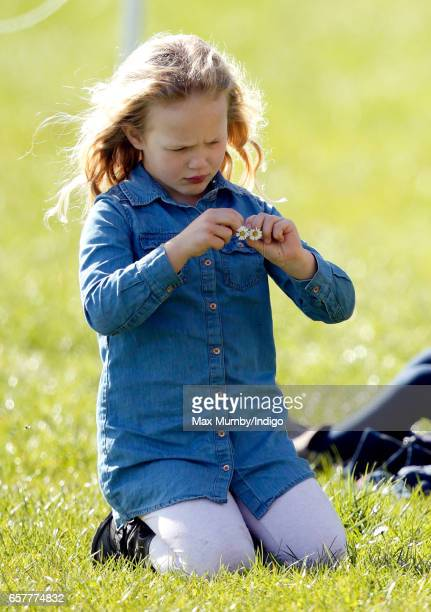 Savannah Phillips makes a daisy chain as she attends the Gatcombe Horse Trials at Gatcombe Park on March 25 2017 in Stroud England