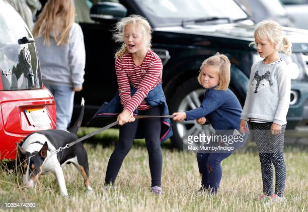 Savannah Phillips Mia Tindall and Isla Phillips struggle to control their grandmother's bull terrier dog as they attend the Whatley Manor Horse...