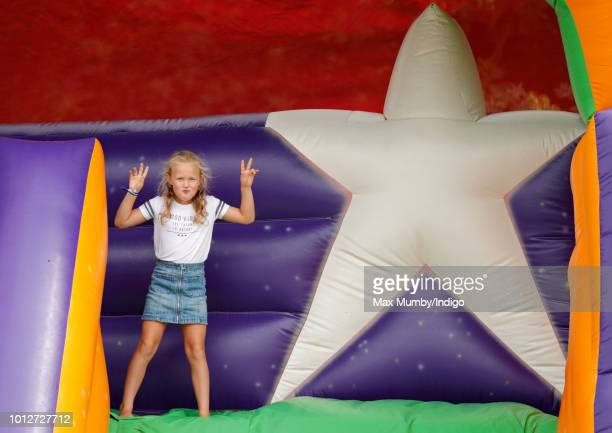 Savannah Phillips plays on an inflatable bouncy slide as she attends day 1 of The Festival of British Eventing at Gatcombe Park on August 3, 2018 in...