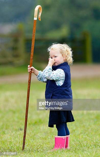 Savannah Phillips plays with her Grandmother's shepherds crook as she and her parents Peter and Autumn Phillips attend the Gatcombe Horse Trials at...