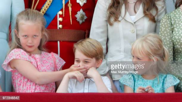 Savannah Phillips puts her hand over Prince George of Cambridge's mouth as they and Isla Phillips stand on the balcony of Buckingham Palace during...