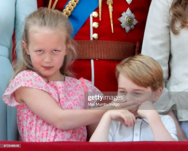 Savannah Phillips puts her hand over Prince George of Cambridge's mouth as they stand on the balcony of Buckingham Palace during Trooping The Colour 2018 on June 9, 2018 in London, England. The annual ceremony, involving over 1400 guardsmen and cavalry, is believed to have first been performed during the reign of King Charles II. The parade marks the official birthday of the Sovereign, even though the Queen's actual birthday is on April 21st.