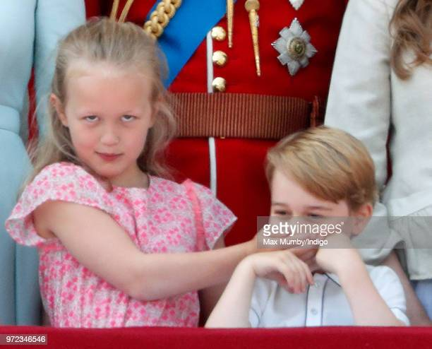 Savannah Phillips puts her hand over Prince George of Cambridge's mouth as they stand on the balcony of Buckingham Palace during Trooping The Colour...
