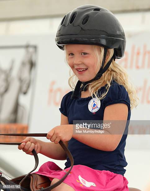 Savannah Phillips rides a mechanical horse as she attends day 1 of the Festival of British Eventing at Gatcombe Park on August 7 2015 in Stroud...