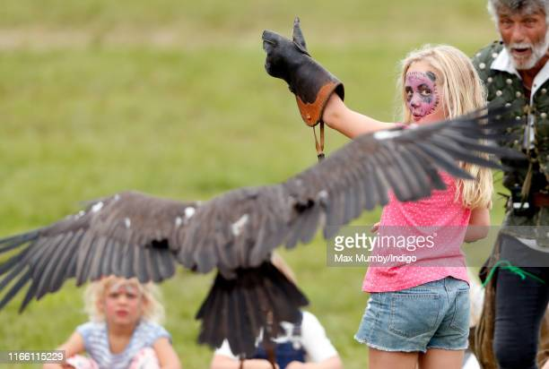Savannah Phillips, seen wearing animal design face paint, takes part in a falconry demonstration as she attends day 3 of the 2019 Festival of British...