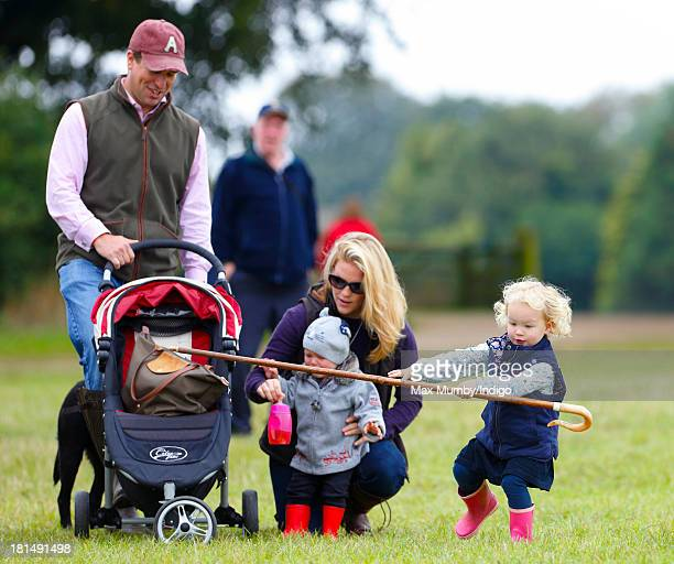 Savannah Phillips takes a tumble whilst playing with her Grandmother's shepherds crook as her parents Peter Phillips and Autumn Phillips look on at...