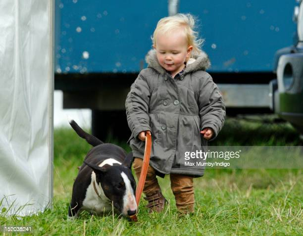 Savannah Phillips walks one of her grandmother Princess Anne The Princess Royal's dogs as she and her parents Peter and Autumn Phillips attend the...