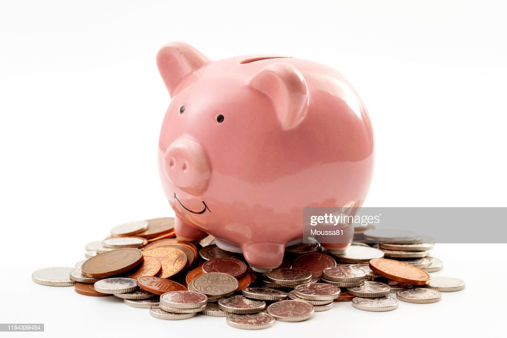Save money, financial planning of personal finances and being thrifty concept theme with a pink piggy bank sitting on a pile of bronze and silver colored coins isolated on white background : Stock Photo