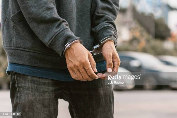 save to boardlooking down at handcuffed male hands on black background - prisoner stock pictures, royalty-free photos & images