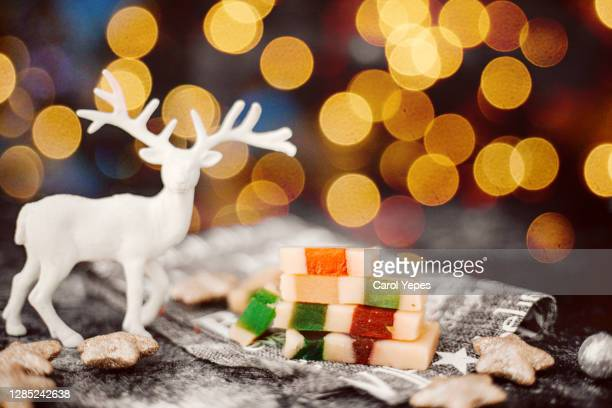 save turrón. almond nougat on wooden board in front of christmas tree - nougat stock pictures, royalty-free photos & images