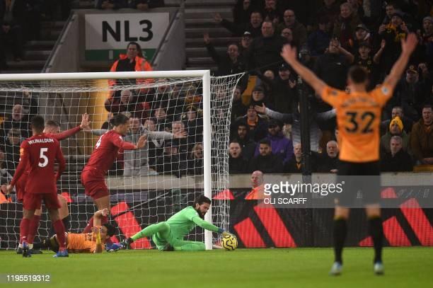 saves a shot Liverpool's Brazilian goalkeeper Alisson Becker during the English Premier League football match between Wolverhampton Wanderers and...