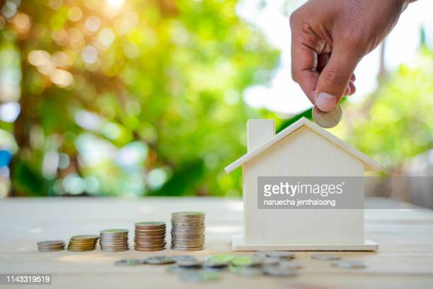 saving money concept. house model and coins stacks on wooden table. save and investment money for prepare in the future. - ��couter photos et images de collection