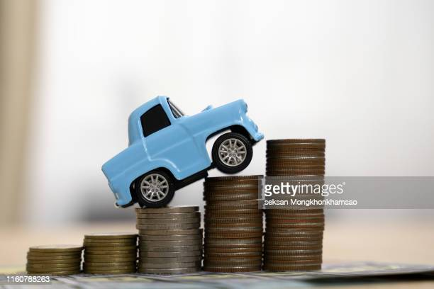 saving money for car or trade car for cash, finance concept title car over a lot of money stacked coins. - erschwinglich stock-fotos und bilder
