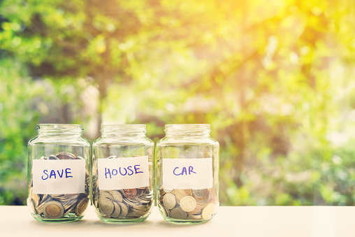 Saving money for house and car concept : Coins in three jars with label. Ideas of saving for a down payment on a car or home that allow buyers to use down payment to reduce overall cost of borrowing. 1038705836