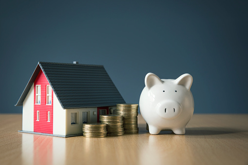 Saving money for house concept with white piggy bank 940283392
