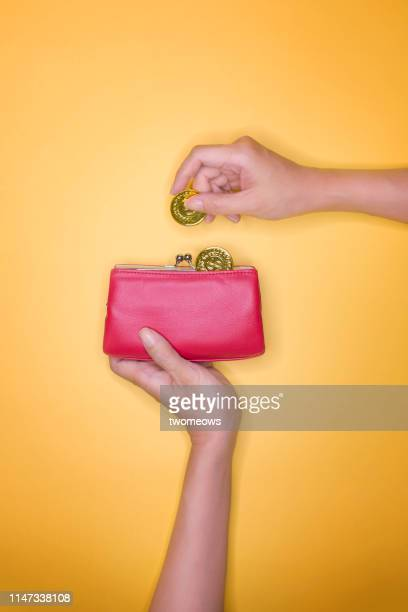 saving or spending money concept image. - gold purse stock pictures, royalty-free photos & images