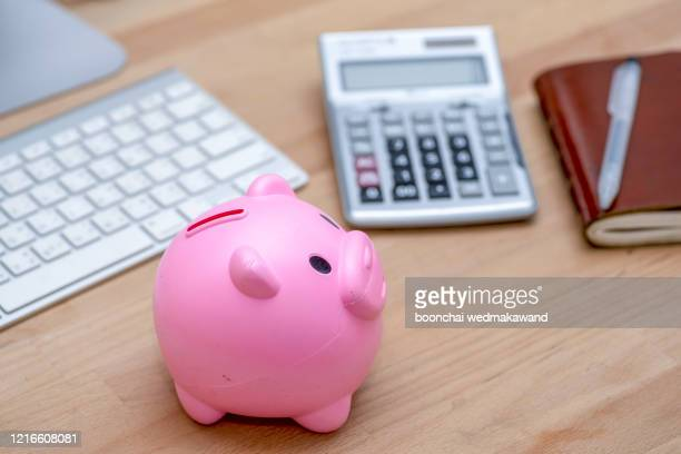 savings and investment concept, pink piggy bank with calculator on pile or economic analysis report chart and graph on office table. - pension stock pictures, royalty-free photos & images