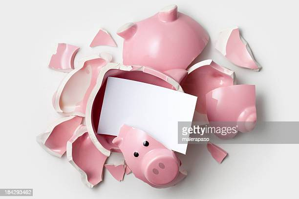 Savings. Broken piggy bank with blank note.