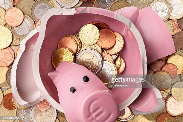 Savings. Broken piggy bank with euro coins
