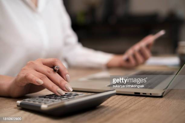 savings, finances and economy concept.close up hand of businesswoman accountant or banker making calculations. - fee stock pictures, royalty-free photos & images