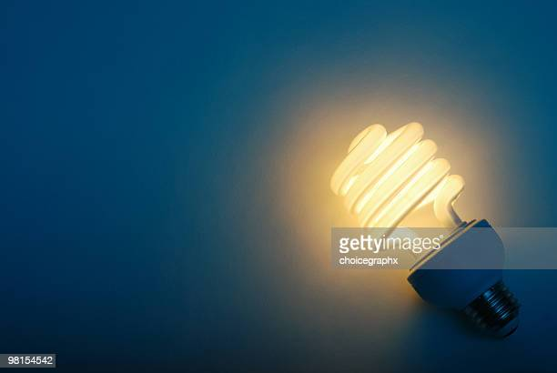 savings with efficient compact fluorescent light bulb - energy efficient lightbulb stock photos and pictures