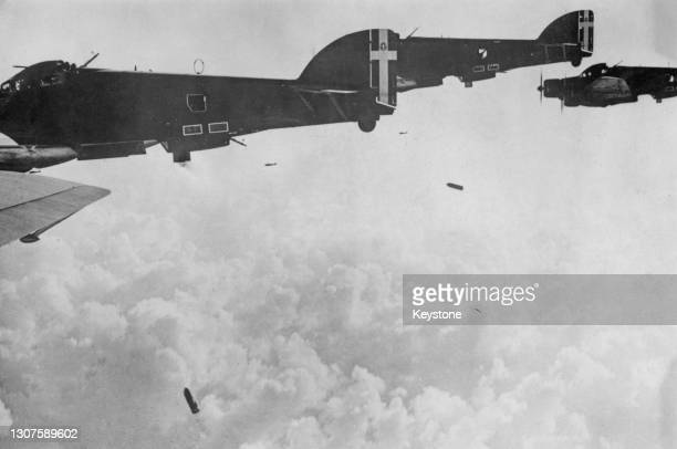Savoia-Marchetti SM79 Sparviero three-engined medium bombers of the Regia Aeronautica release their payload of bombs during an attack on the city of...