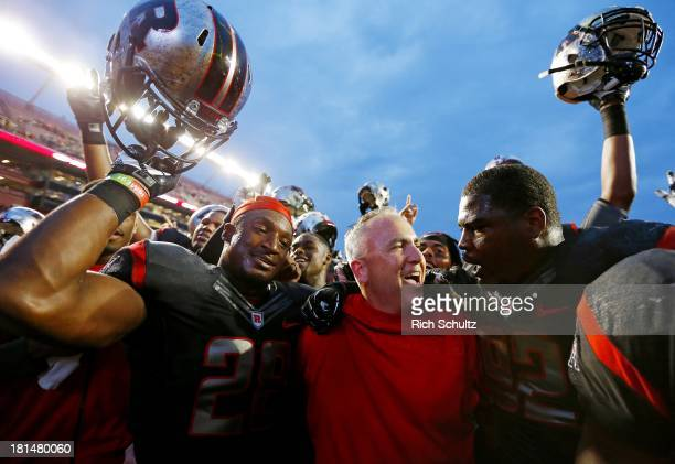 Savon Huggins, head coach Kyle Flood and Jamil Merrell of the Rutgers Scarlet Knights celebrate their 28-24 victory over the Arkansas Razorbacks in a...