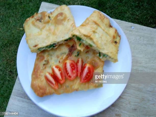 savory and spicy martabak or omelette food with sliced tomatoes on a white plate with a background of antique wood or rustic wood - tortilla de patata fotografías e imágenes de stock