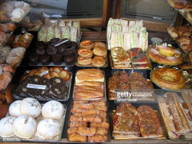 Savory and sweet baked items for sale in the window of a bakery in Barcelona, Spain