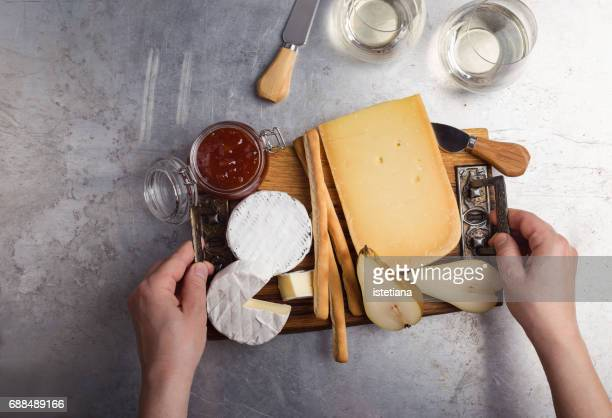 Savory dessert. Female hands placing cheese platter