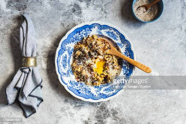 savoury oats with poached egg, fried shallots and grated parmesan cheese - hartig voedsel stockfoto's en -beelden