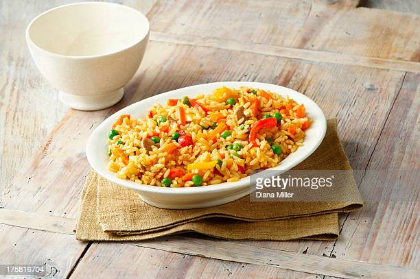 Savoury rice with, peas, red and yellow peppers, carrots and mushrooms in white serving dish