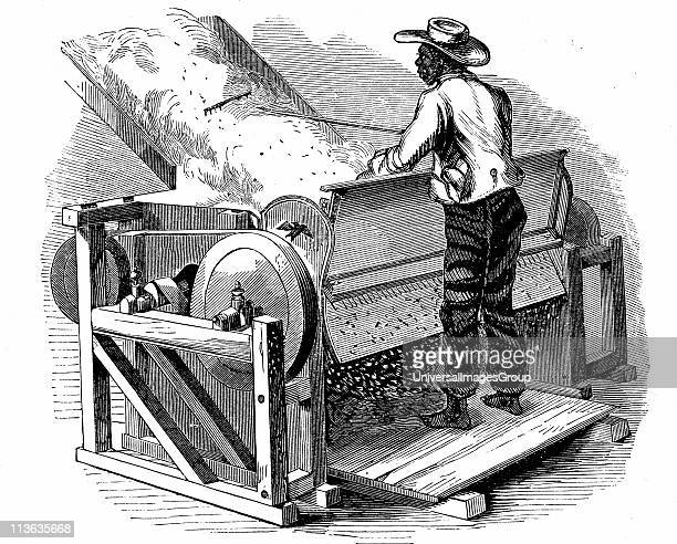 Saw gin for cleaning cotton being operated by barefoot black labourer Southern States of USA Eagle gin improved form of Whitney gin Wood engraving...