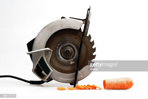 saw sitting beside cut up carrot slice, on white background - circular saw stock photos and pictures