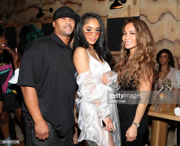 Saweetie poses with her parents Jonathan and Trinidad at her 'High Maintenance' Listening Event on March 12 2018 in Hollywood California