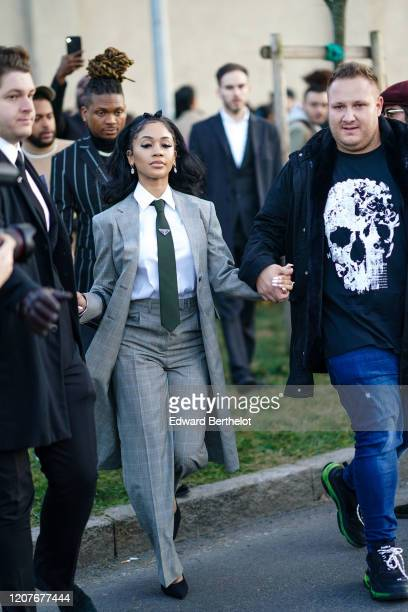 Saweetie wears a gray jacket earrings a white shirt a tie outside Prada during Milan Fashion Week Fall/Winter 20202021 on February 20 2020 in Milan...