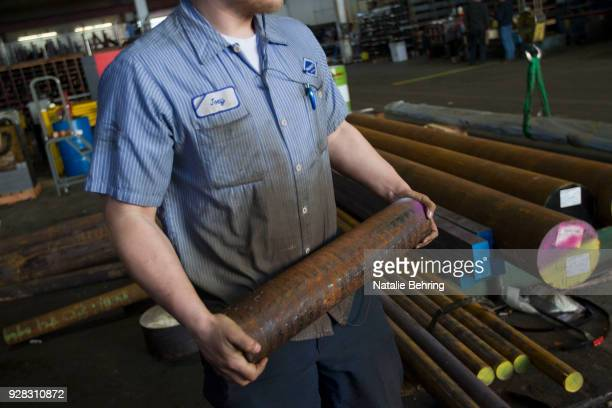 A sawyer carries a cut of machine grade steel to be shipped throughout the Pacific Northwest at the Pacific Machinery Tool Steel Company on March 6...