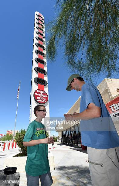 Sawyer DeShon of Arizona gets help from his father Ryan Sawyer as they take photos in front of a 134-foot-high electronic sign displaying the...