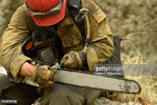 Sawyer Jack Nerison a member of the Montana Bitterroot Hotshots takes a moment to sharpen the teeth on his chain saw as he and other members used...