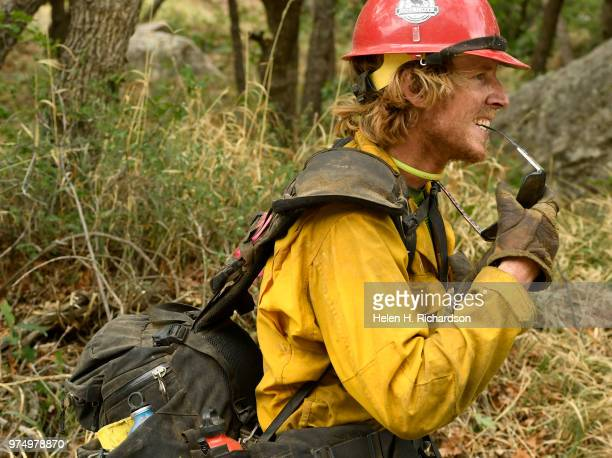 Sawyer Luke Brehm a member of the Montana Bitterroot Hotshots finishes cutting in a shaded fuel break and a hand line around a home along County Road...
