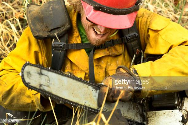 Sawyer Luke Brehm a member of the Montana Bitterroot Hotshots takes a moment to sharpen the teeth on his chain saw as he and other members used saws...