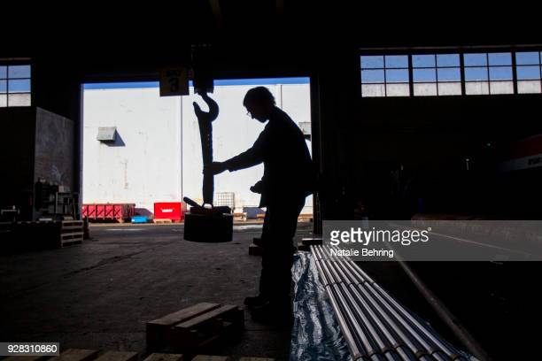 A sawyer uses a giant magnet to move a cut of machine grade steel at the Pacific Machinery Tool Steel Company on March 6 2018 in Portland Oregon...