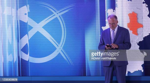Saxony Anhalt's State Premier Reiner Haseloff, top candidate of his conservative Christian Democratic Union's party, checks his smartphone as he...