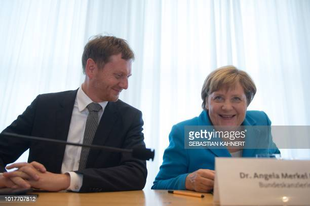 Saxony's Prime Minister Michael Kretschmer and German Chancellor Angela Merkel arrive for a meeting of the CDU party in Saxony state in Dresden on...