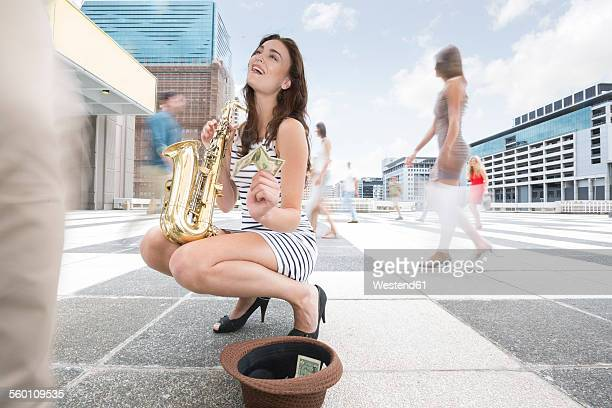 Saxophone player accepting a donation between a crowd of people in a city