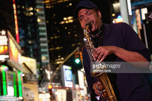saxophone player on broadway - jazz stock pictures, royalty-free photos & images
