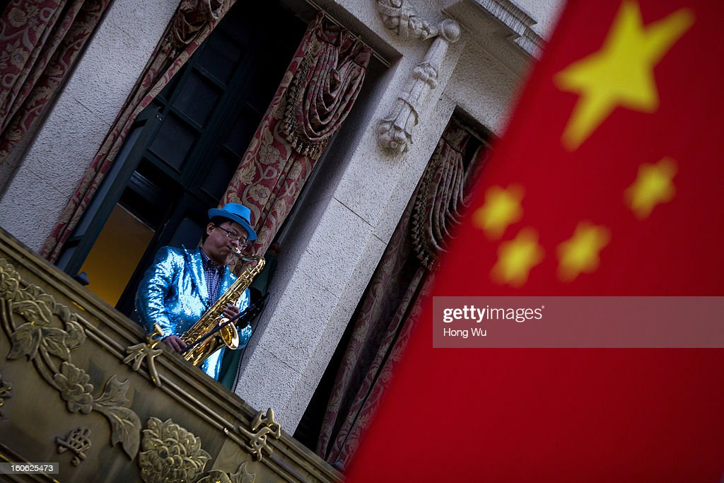 A saxophone player performs near by a Chinese national flag in Nanjing Road Walking Street on February 3, 2013 in Shanghai, China.