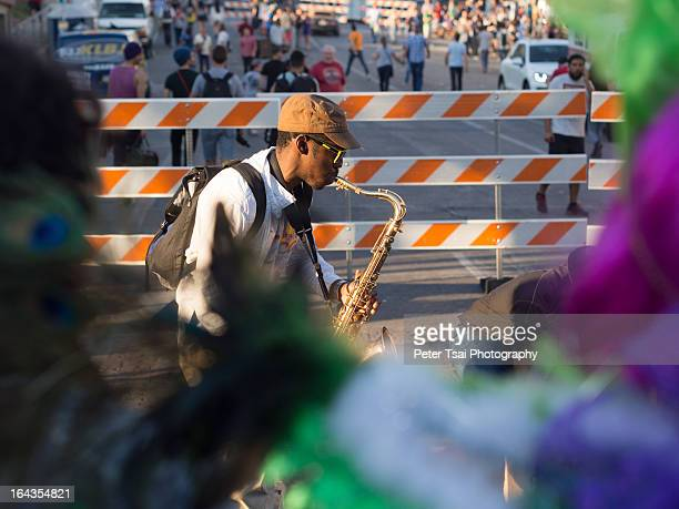 CONTENT] A saxophone player plays his horn in a mardi gras / carnival environment on 6th Street in downtown Austin Texas during SXSW