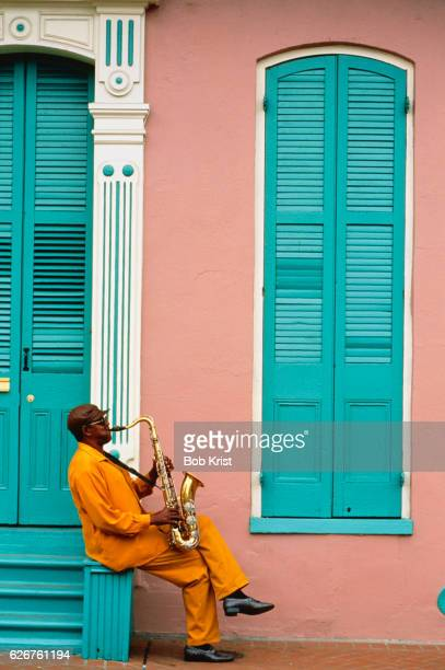 saxophonist playing outside building in the french quarter - jazz music stock pictures, royalty-free photos & images