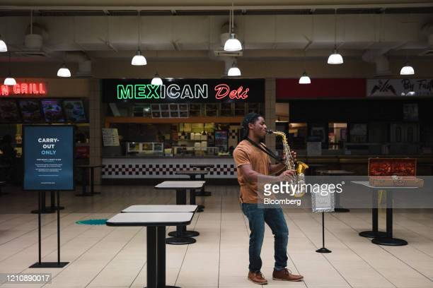 Saxophonist plays in the take-out only food court in the re-opened Anderson Mall in Anderson, South Carolina, on Friday, April 24, 2020. After...